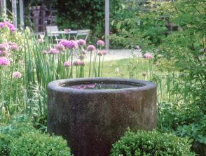 Landhausgarten mit geschütztem Sitzplatz unter einer Pergola