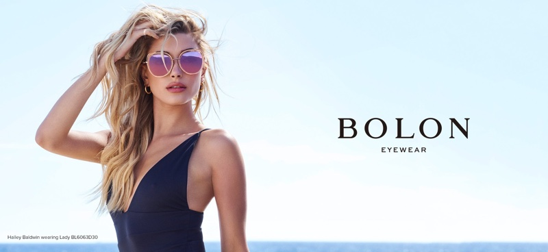 Wearing a swimsuit, Hailey Baldwin poses in Bolon Eyewear 2018 campaign