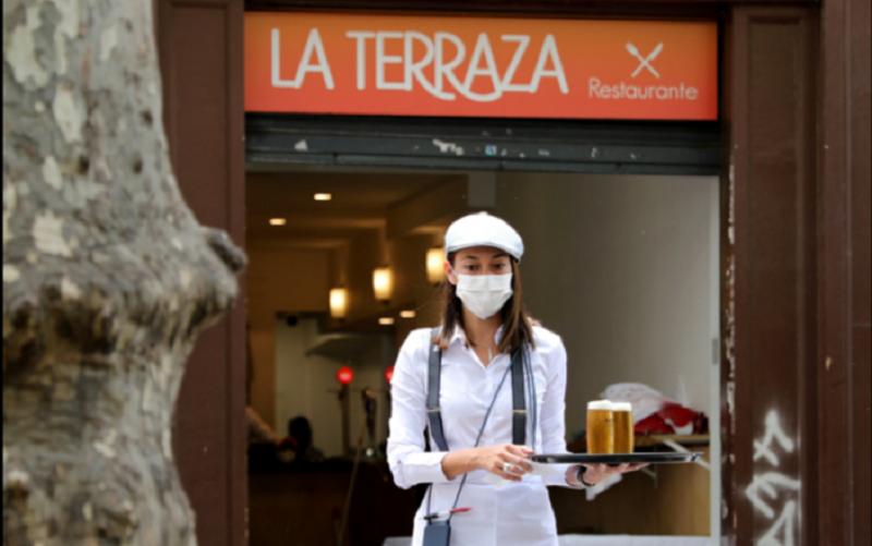 Una camarera con máscara protectora lleva bebidas a los clientes en una sección de asientos al aire libre de un restaurante en Ramblas, ya que algunas provincias españolas pueden aliviar las restricciones de bloqueo durante la fase uno / REUTERS