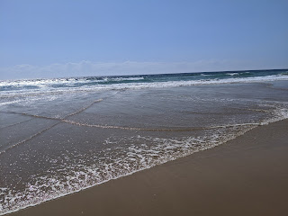 A sunny beach with flat waves and wide open horizon.