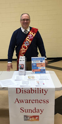 Leo Yates stands behind a table with brochures about disability awareness
