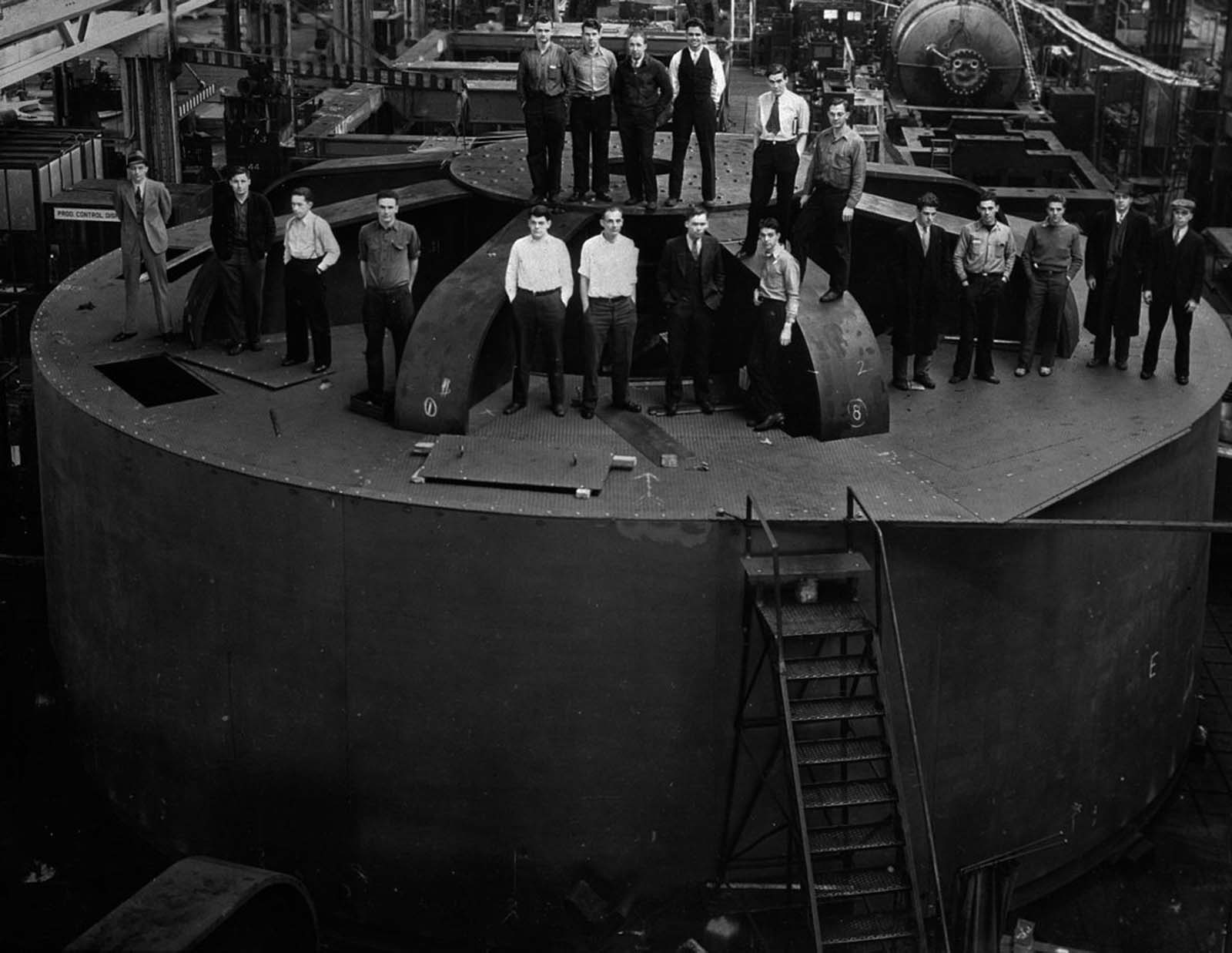 Student engineers stand atop one of the 2 million-pound hydroelectric generators for the dam at the General Electric factory in Schenectady, New York. 1935.