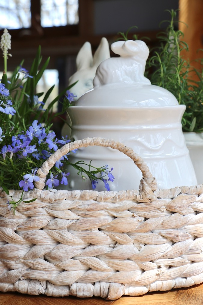 A large white washed basket, filled with a blue and white spring arrangement, protects an antique French Country table from damage