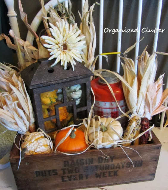 A rustic crate decorated with fall decor.