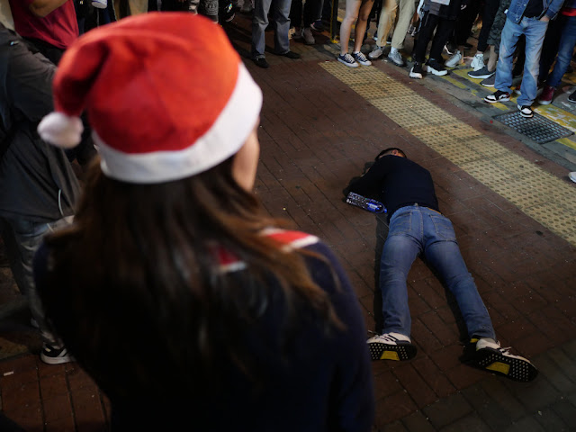 woman wearing a Santa cap looking at a man on the ground