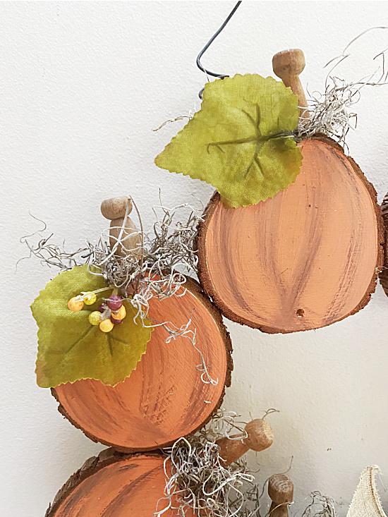 wood slice pumpkins with leaves and berries