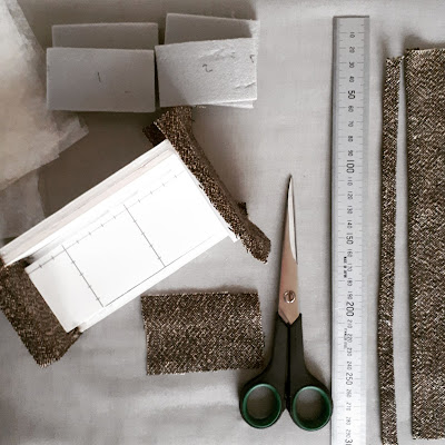 FLat lay of a half completed one twelfth scale modern miniature sofa, scissors, ruler and fabric pieces.