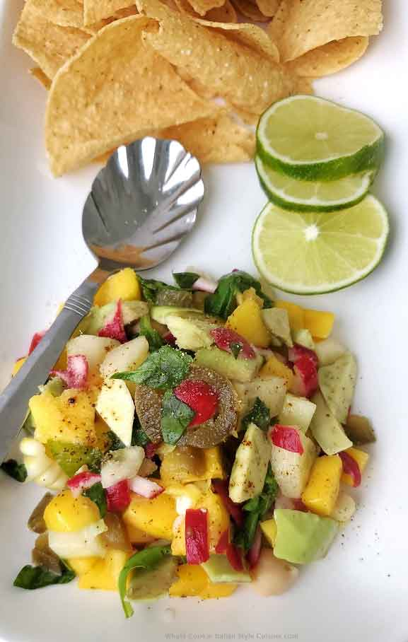 this is a mango salsa for topping meats and seafood with vegetables diced