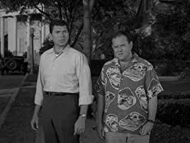 Black and white film still of 2 men in 1950's clothes standing in a front yard
