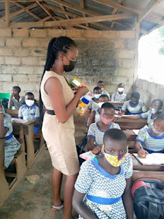 She helped her students by making new school uniforms for them and buying them writing materials