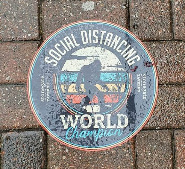 Social distancing world champion floor sticker at a pub in Chesterfield