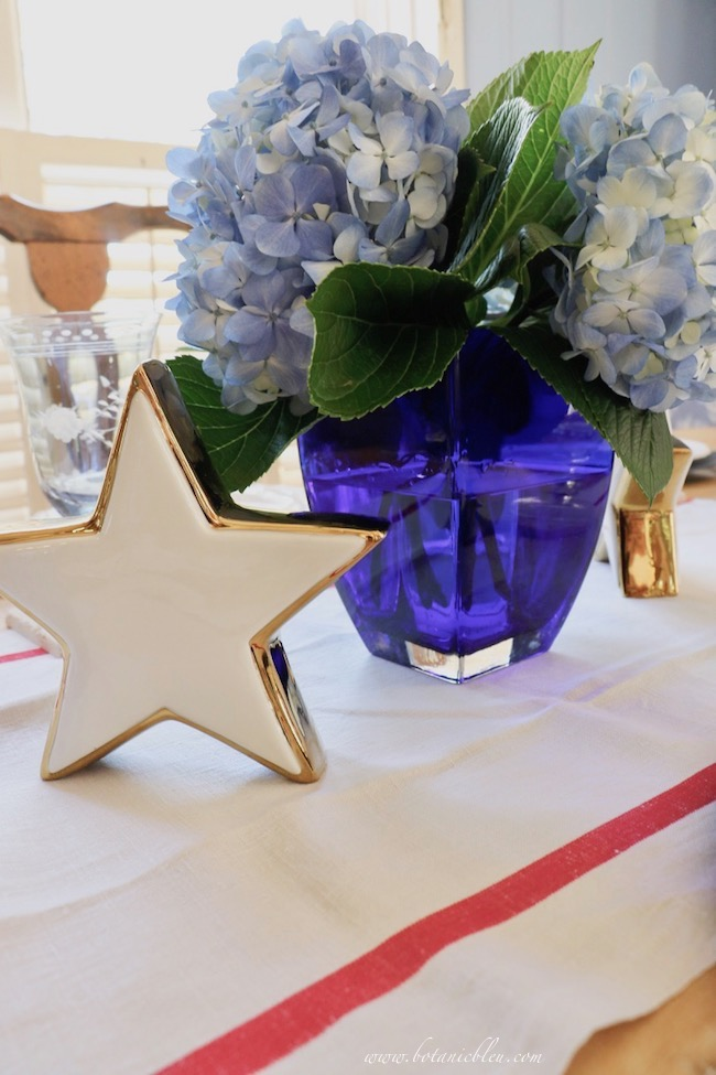 set a stars and stripes table setting with white stars, French vintage linen towel, blue hydrangeas