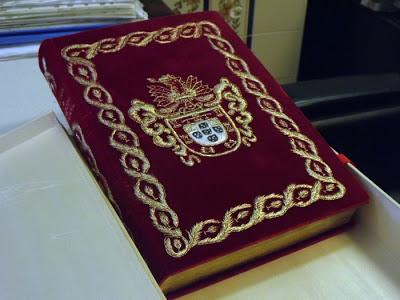 livro com capa decorada com o brasão de Portugal