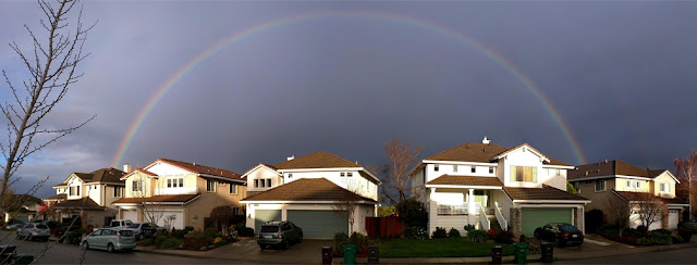 Full rainbow above neighborhood houses against an overcast sky. Garbage bins are in front of the houses.