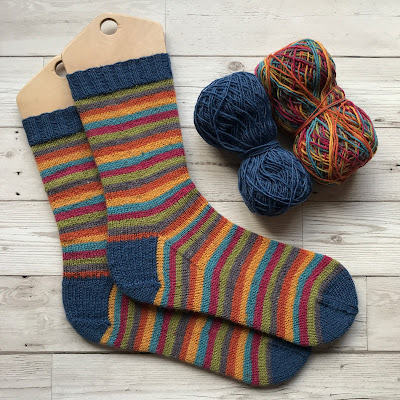 Pair of stripey handknitted socks with contrast heels, cuffs and toes, next to two half used balls of wool