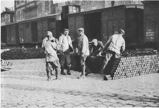 Black and white photo of a brick-building factory with containers in front of it. In front of the container, one the right side stands a stack of cylinder shaped military munition. In front of the container and to the left of the stack stand six men wearing factory boots, thick winter jackets and berets.