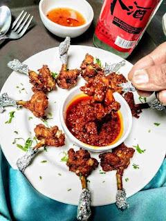 Serving chicken lollipop with Schezwan sauce