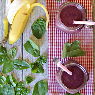 Blueberry and Beet Smoothie on a red striped towel with peeled banana and tablespoon of peanut butter.