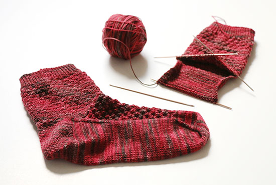 Completed hand knit red wool sock next to one in progress on metal double point knitting needles and a ball of yarn on a white background.