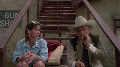 The Texas Chainsaw Massacre 2 1986 movie still where Caroline Williams and Dennis Hopper talk on a staircase