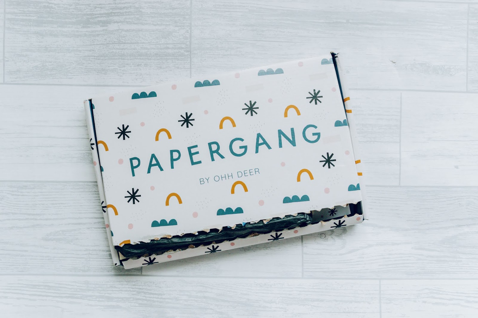 A Papergangbox closed on a white wood floor.