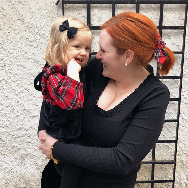 Want to match with your toddler daughter for the holidays this year? Try coordinating her top and your hair bow. Picking similar color schemes with matching plaid elements is a fun way to coordinate your holiday outfits.