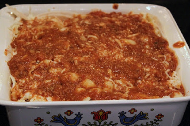 Tortilla layered and filled with melted cheese, meat and refried beans in a casserole dish baked