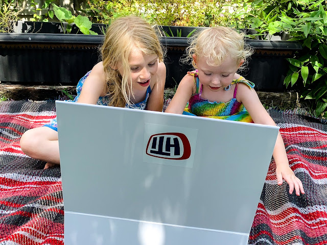 Sisters sitting on a picnic blanket looking in a white box with an HTI label