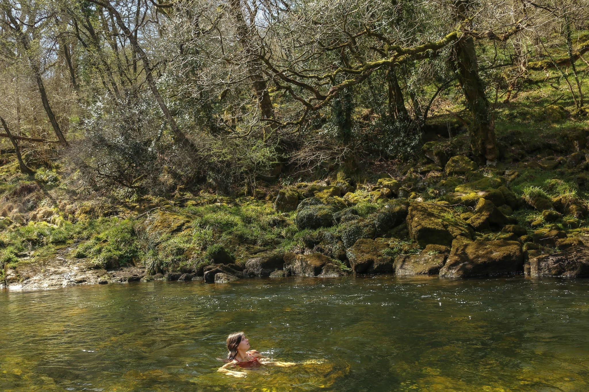 Girl wild swimming in the river Dart in Dartmoor