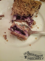A close shot of the blueberry cheesecake pie on a white plate. Some of it is on the spoon on the plate (which is somewhat covered im crumbs).