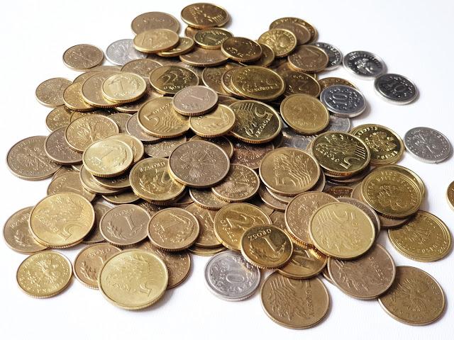 na zdjęciu na białym tle widać stos monet o nominałach 1,2,5,10,i 20 groszy