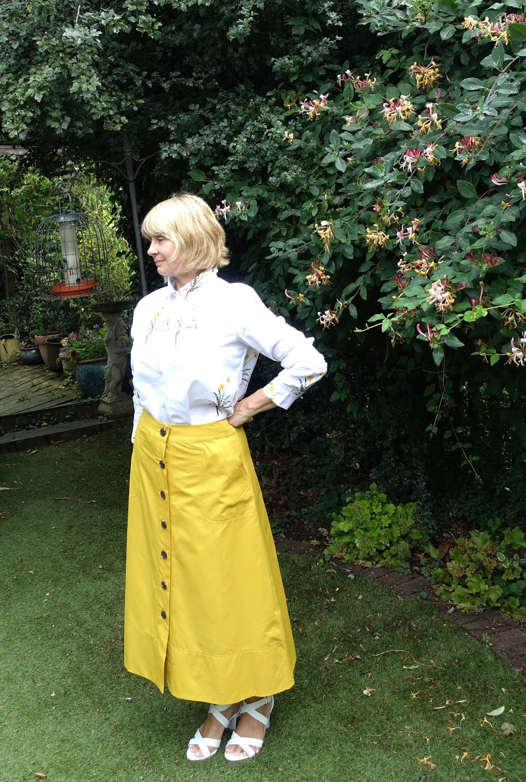 Full length picture of over-50s woman in yellow midi skirt, white sandals and white shirt with yellow floral print
