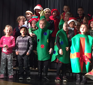 Students in Christmas costumes standing up singing