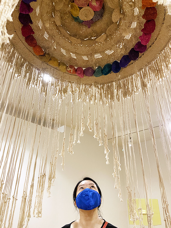 Solo Lisa looks up at a woven and crocheted art installation hanging from the ceiling. Part of the 'Modern in the Making: Post-War Craft and Design in British Columbia' exhibit at the Vancouver Art Gallery.