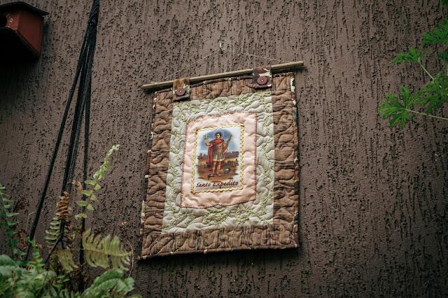 quadro de santo expedito em patchwork pendurado na parede