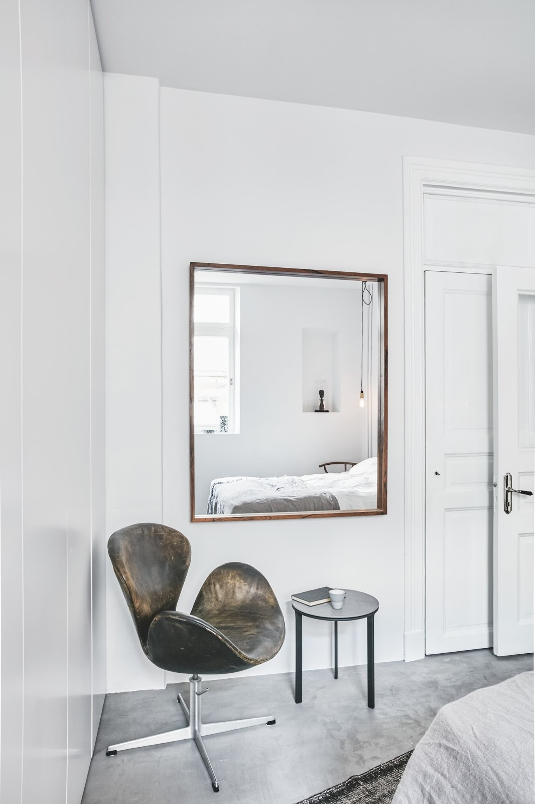 swan chair inside of an minimalist nordic bedroom