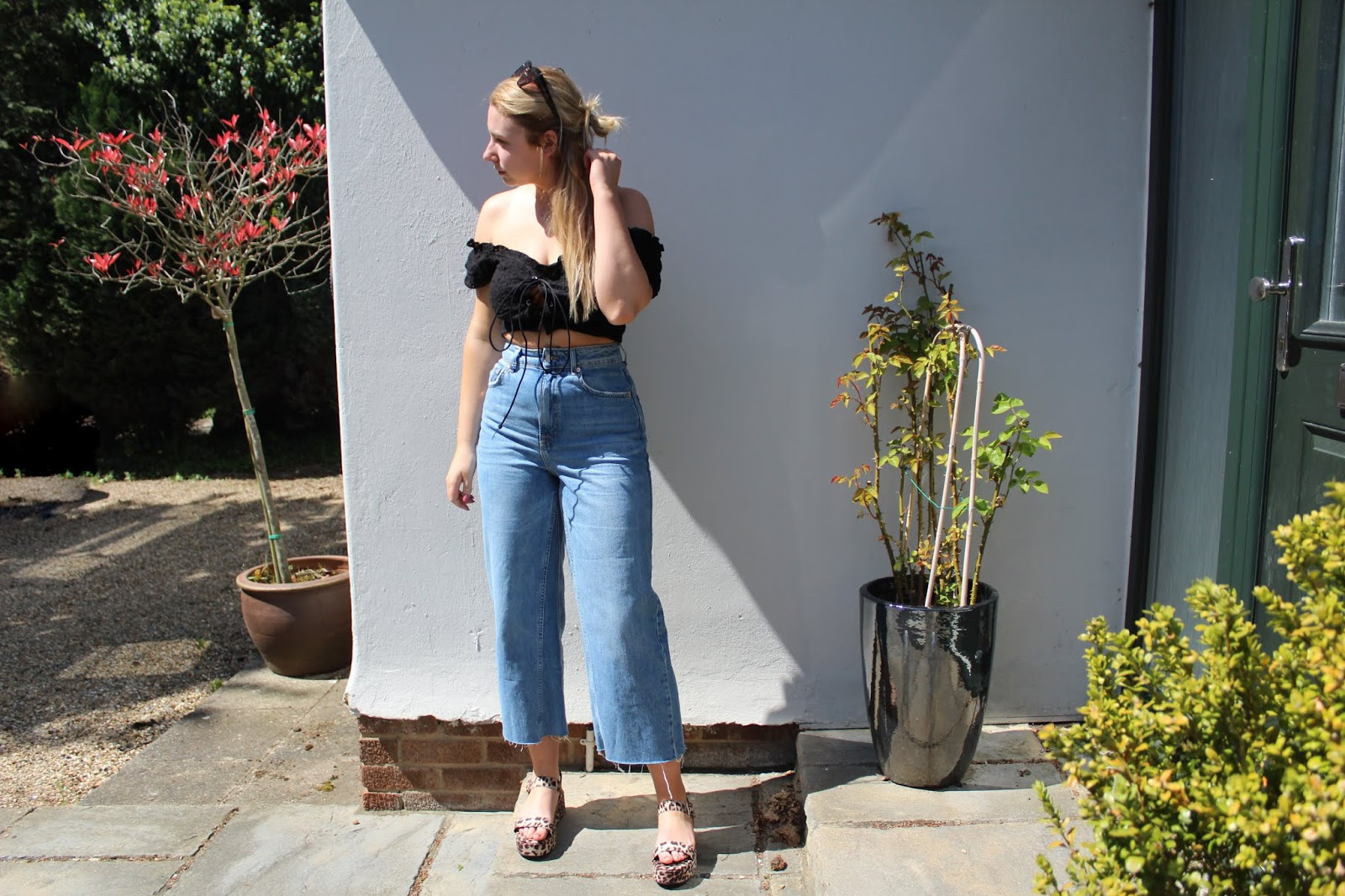 Outside against white wall wearing black top and jeans
