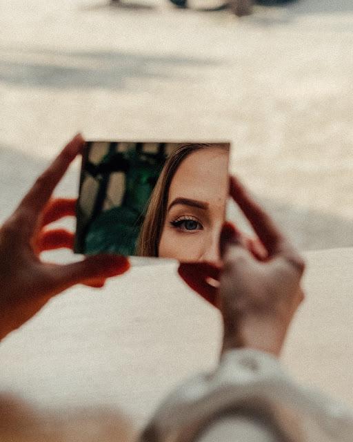 Mulher olha para seu rosto por meio do espelho