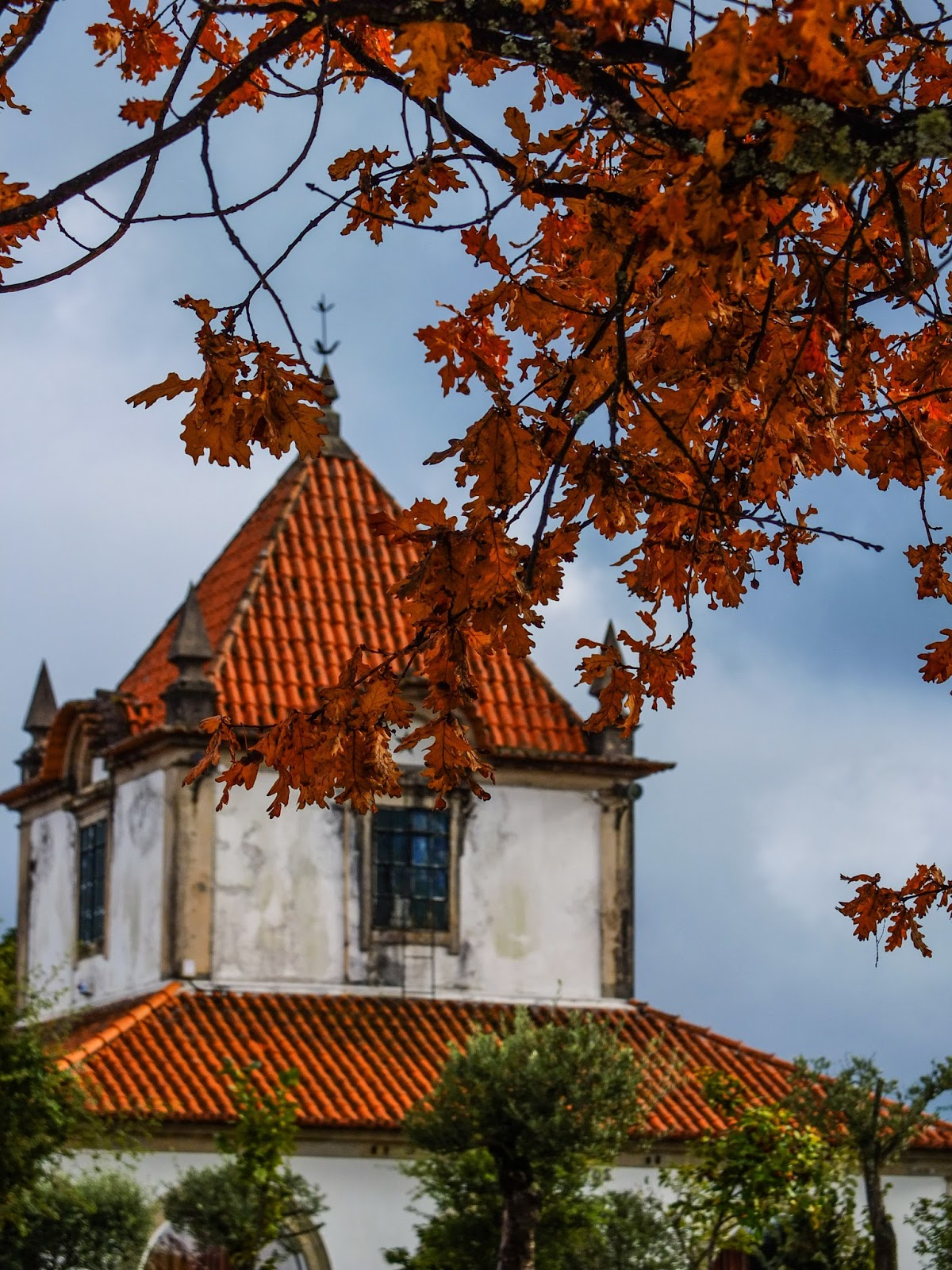 Beautiful building with a terracotta roof pictured under an oak tree in the Sameiro Sanctuary.