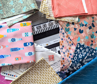 a selection of modern quilting fabrics laid out randomly
