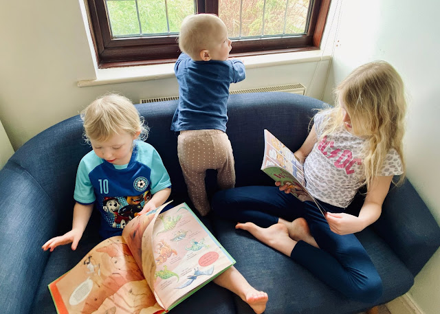 3 children on a sofa, a young boy is standing on it and looking out of the window, the girls are looking at books