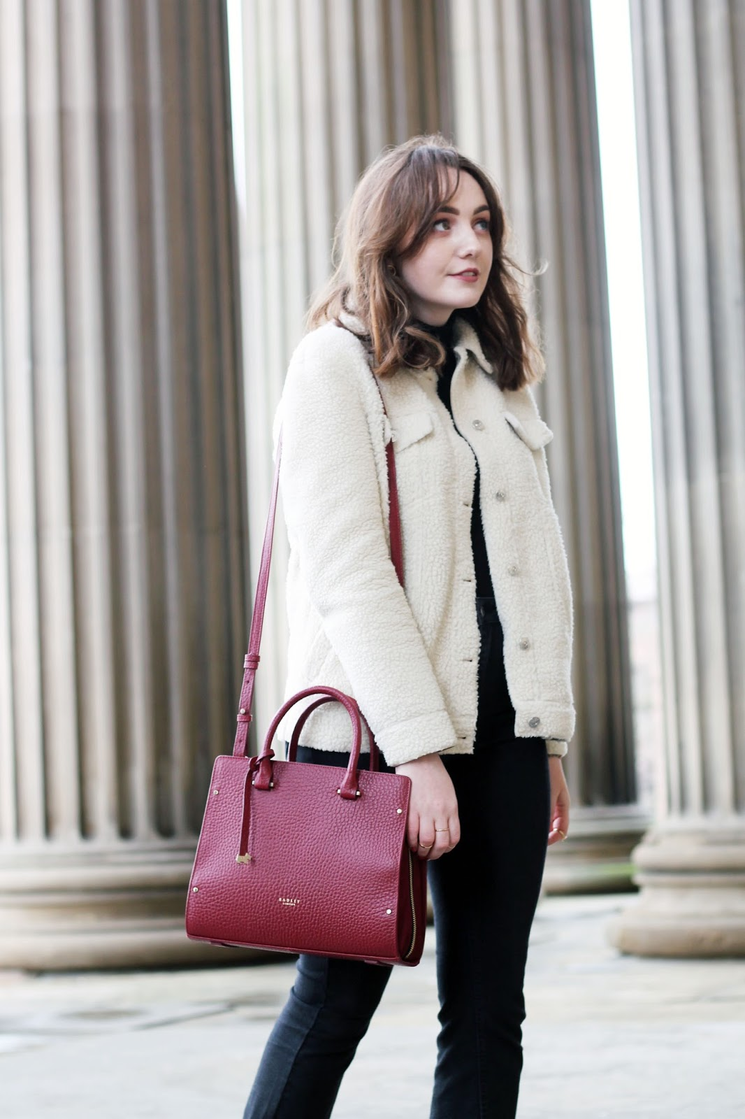 UK style blogger Allie Davies in cream borg trucker jacket, black polo neck jumper, black raw hem cropped jeans and red burgundy Bradley handbag