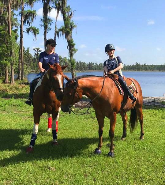 Bryanna is seated atop a brown horse. They stand on a field of bright green grass, a lake behind them, a fellow horse and rider beside them