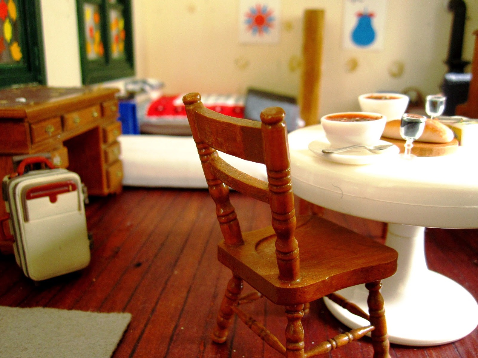 Interior of a miniature holiday home with a suitcase in one corner and a table set with two bowls of soup and glasses of wine, and a loaf of crusty bread in the other.