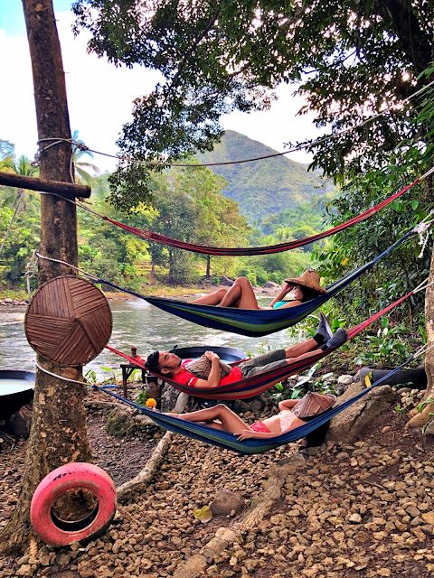 Three friends cozy up having a nap on a hammock