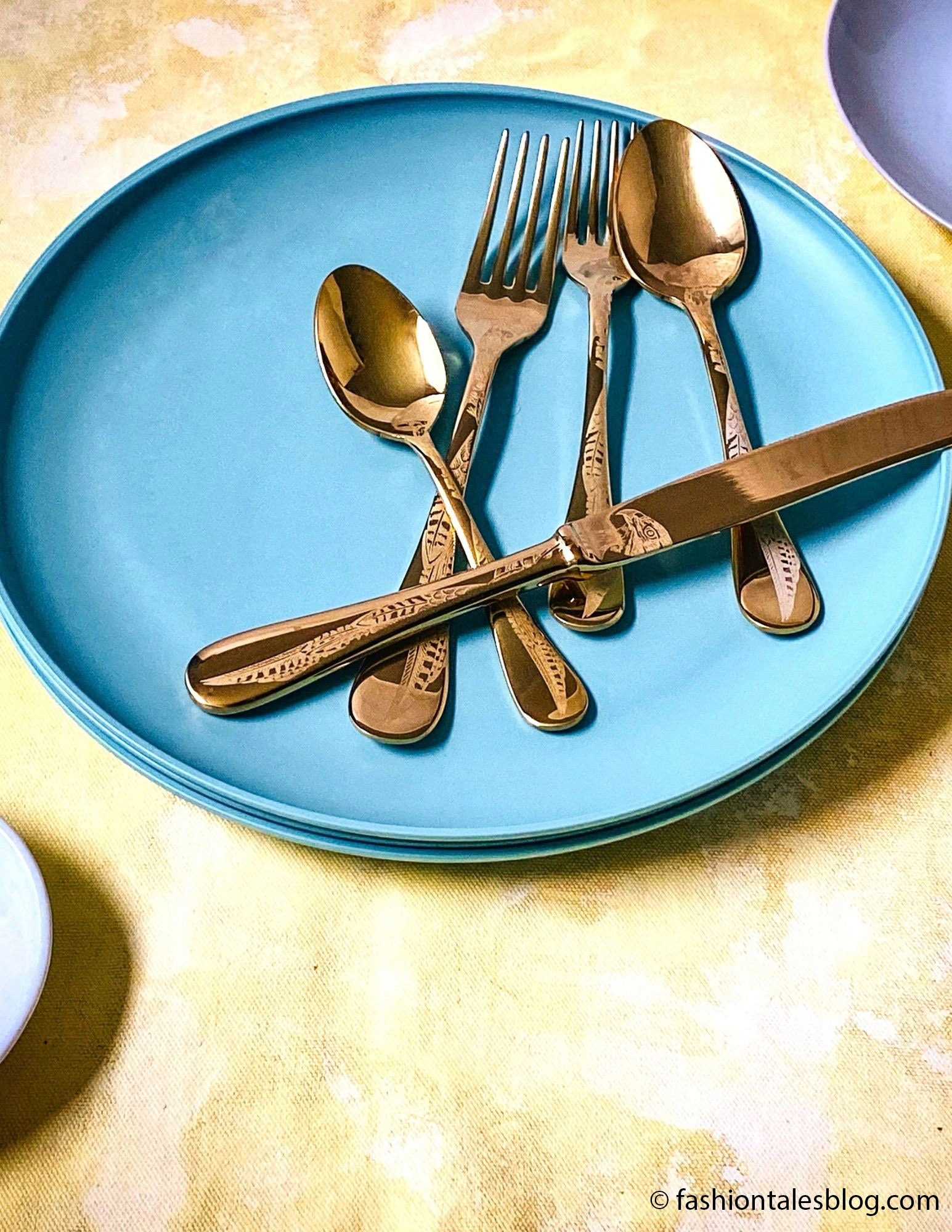 GOLD CUTLERY ON A PLATE