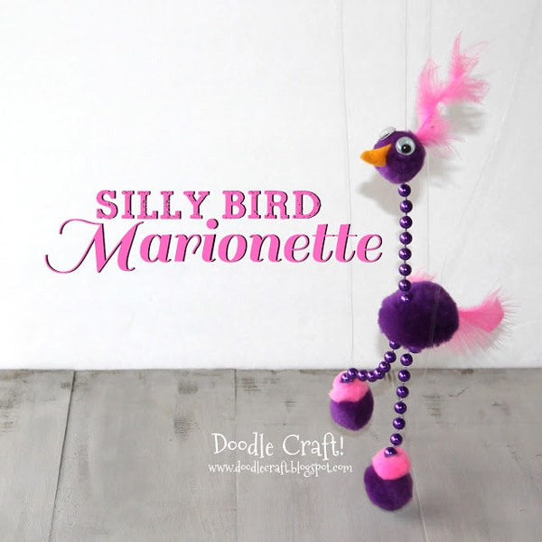 Pom pom Marionette bird made with mardis gras beads, pom poms and feathers.