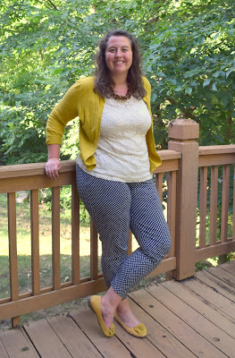 an outfit with a lace shirt, a mustard cardigan, a tortoiseshell necklace, navy polka dot pants, and mustard flats