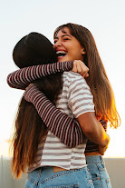 Two caucasian women both wearing striped topped giving each other a hug