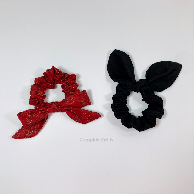 A red scrunchie with a bow tied on it and a black bunny ear scrunchie.